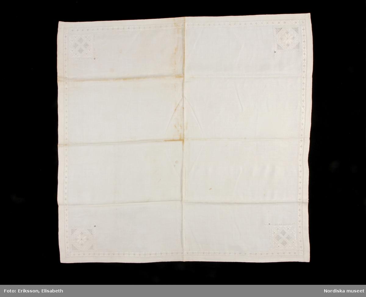 """Kvadratiskt kläde i handvävt  linne. Invikt fåll, 2,5 cm bred, en 1,7 cm bred broderad bård i fållkant. Kantbården består av rombiska former med dubbel utdragssöm, rätlinjig plattsöm mellan formerna. Enkel utdragssöm i kanterna. Två motställda sidor har en kantbård som är 1,7 cm bred och övriga 2 cm bred. Kvadratiska hörnbroderier, ca 9 x 9 cm, i alla hörn. Broderierna består av rombiska, kvadratiska och rektangulära former i utskårssöm, stopphålssöm och rätlinjig plattsöm. Enkel utdragssöm i kanterna. Broderierna utförda i vitt lingarn. Alla hörnmotiv har olika mönster. I varje hörnsnibb en langetterad hank, troligen avsedd att fästa mindre tygdekorationer, s.k. vippor. Klädet är handsytt. Anm: Gulnat i veck.  Utdrag ur Svensson Sigfrid, (1935). Skånes Folkdräkter, en dräkthistorisk undersökning 1500 - 1900. Stockholm: Nordiska Museets Handlingar: 3, sid. 262 - 263: """"Härmed kan sammanställas Linnés uppgift från Göinge: 'Torrklädet' är et linne armkläde, wid kanterna genombåradt och sydt samt med spetsar kantadt och med wippor i hörnen utsiradt'. Dessa benämningar - 'näsduk', 'torrkläde' och 'armkläde' - förekomma i bouppteckningarna redan vid 1700-talet början och åsyfta tydligen då en duk, som burits på armen eller hållits i handen...Från Ö. Göinge omtalar Eva Vigstsröm, att till fästmögåvorna också hörde en 'kinnaklud' och enligt beskrivning var denna av fullkomligt samma utseende som armklädet. Om dess användning säges: 'Denna klut bands helt utbredd öfver brudens hår, då hon red eller åkte till kyrkan.' Samma bruk har förekommit i Ingelstad: 'Under resan till och från kyrkan hade bruden öfwer locken, liksom öfwer kluten, ett 'hyeklä', ett fyrkantigt tygstycke af linne med genombrutet arbete.'. Enligt Wistrand användes samma plagg även vid kyrkobesök och resor och Svanander omtalar hyeklädets användning till sorgdräkten, fig 242. Att armkläde och hyekläde förkomma samtidigt i bouppteckningarna torde bero på en senare differentiering. Ett och samma slags linneduk"""