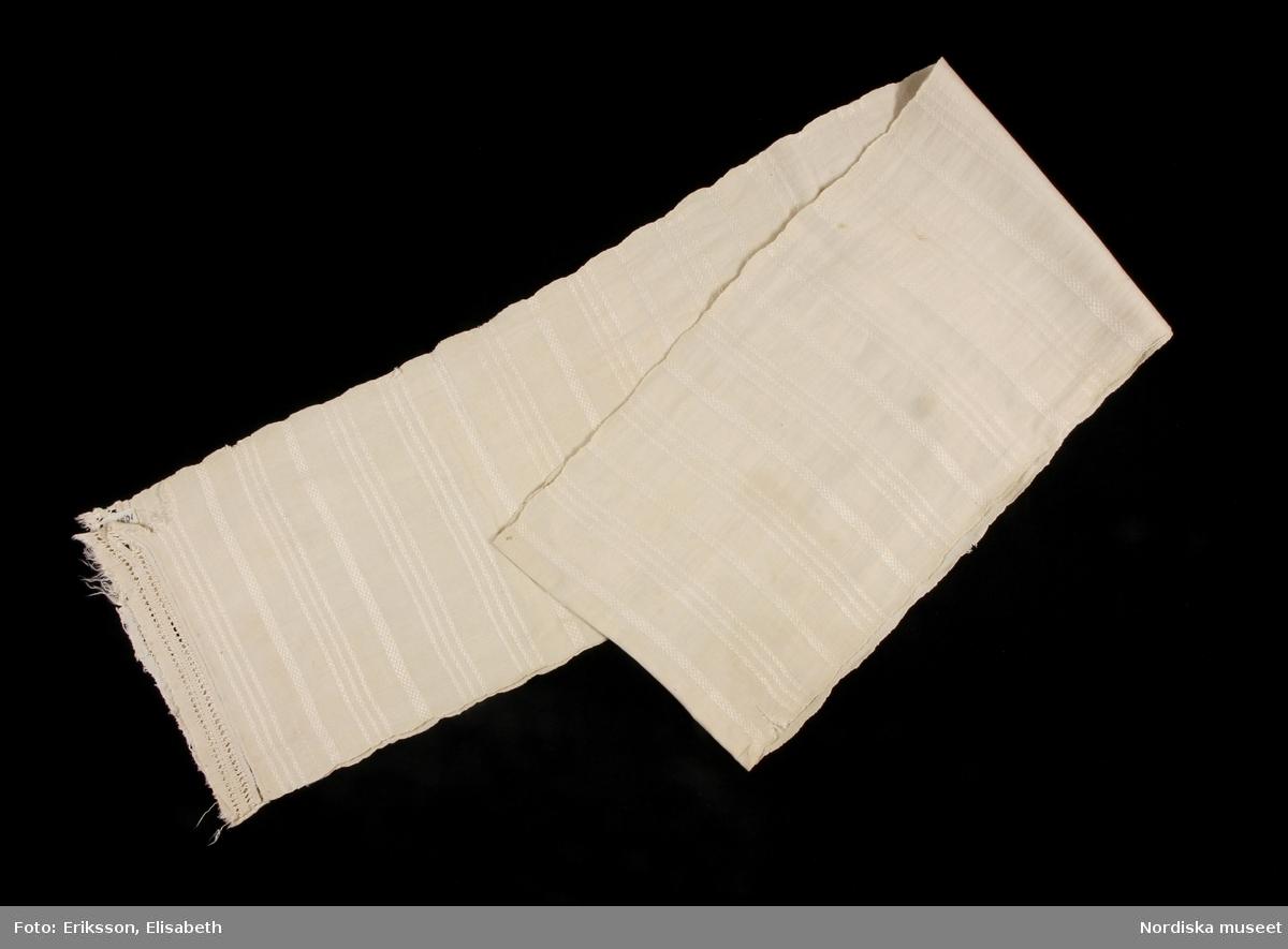 Bårkläde i linne. Handvävt, tuskaftsbotten med ränder i grövre kvaliteé i olika kypertvariationer, 3 smala, ca 0,8 cm och en bredare, ca 1,3 cm, i rapporter över hela längden. Varje rapport ca 7 cm bred. I kortändarna vidsytt linnetyg, ca 4,5 cm brett. Tygbitarna har bårder i utdragssöm, i ena änden är tygbiten skarvad, fransiga kanter. Bårklädet har stadkanter i båda sidorna. /Inga-Lill Eliasson 2007-12-18