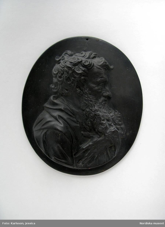 Bröstbild, höger profil, av äldre man med skägg. Håller vänster hand på bröstet.