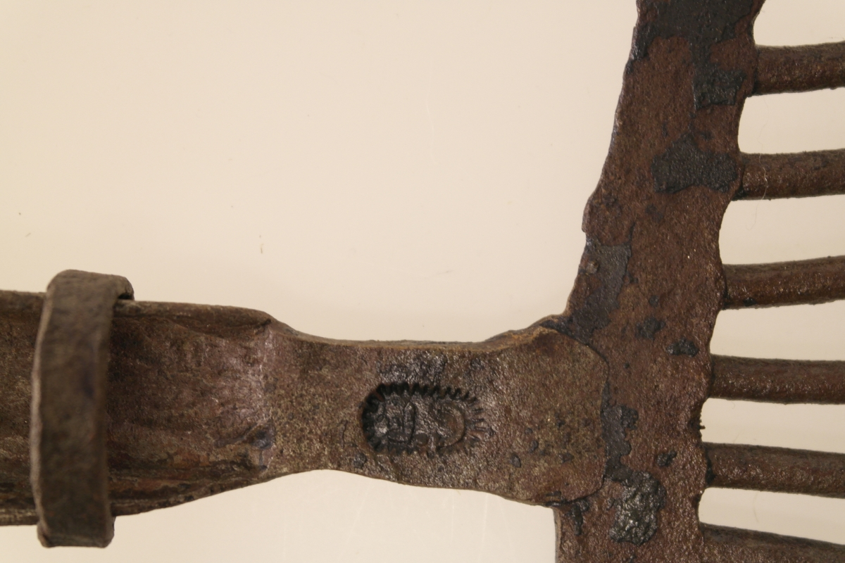 Lyster av smidd jern. Gaffelform med 10 tinder, utstyrt med mothaker. Festeanordning m/ring for evt. treskaft. Innpreging på jernskaft.