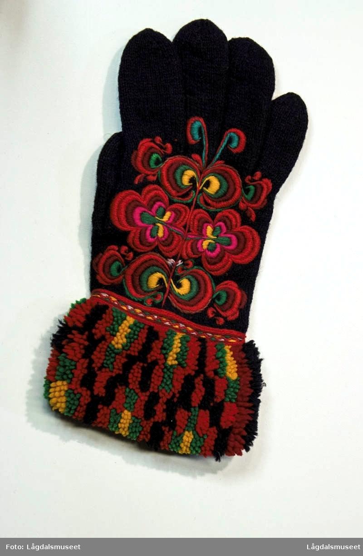 Brodert dekor i flere farger. Motivet er ulike blomster og ornamenter brodert i plattsøm. Mansjettene er dekorert med flosskant.