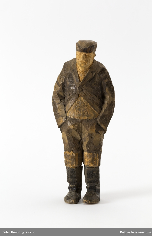 KLM 45932:2 Skulptur, av trä, målad. Figur i form av en stående man. Han har båda händerna i byxfickorna. Klädd i huvudbonad, jacka, väst och byxor med lappar på knäna, samt stövlar. Signerad på ryggen, H.C. Målad i bruna nyanser och svart. Tillverkad av Helge Rugland, f. Carlsson.