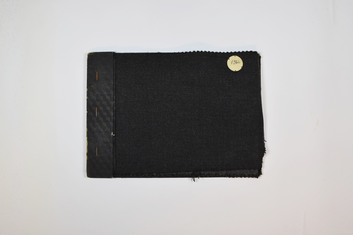 Prøvehefte med 4 prøver. Middels tykke melerte stoff med fiskebensmønster, skrå striper eller prikker. Stoffene ligger brettet dobbelt i heftet slik at vranga dekkes. Stoffene er merket med en rund papirlapp, festet til stoffet med metallstifter, hvor nummer er påført for hånd. Heftet har en stiv bakplate og en papp-plate der heftet er stiftet som dekker ca. 5 cm av forsiden.   Stoff nr.: 1366, 1366A, 1366B, 1366C.
