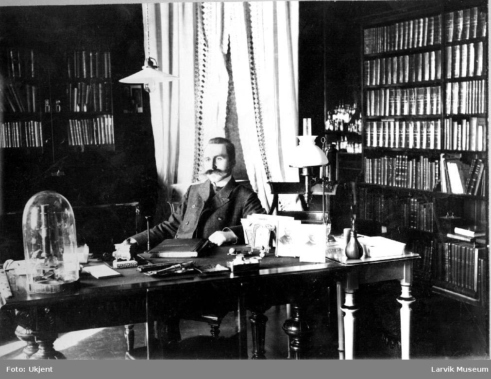 Hans Teilman Hansteen sittende i et kontor/bibliotek