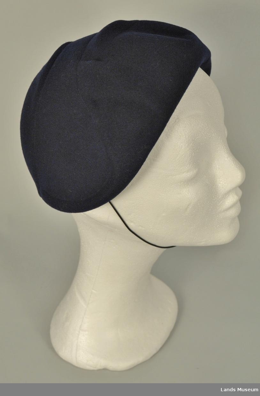 Ullfilt. Presset hatt uten brem. Figurstriper i pullen. Ripsbånd og hattestrikk.