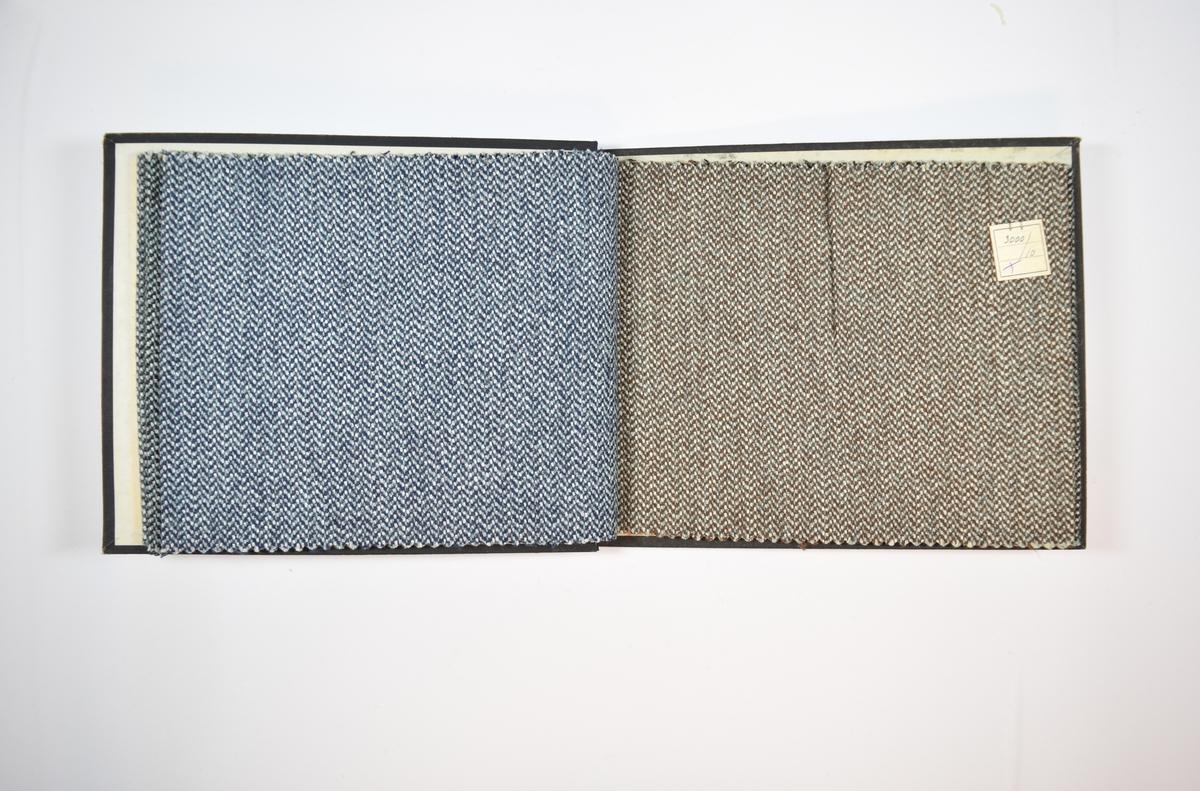 Rektangulær prøvebok med fem stoffprøver og harde permer. Permene er laget av hard kartong og er trukket med sort tynn tekstil. Boken inneholder middels tykke flerfargede stoff med prikker/fiskebensmønster. Kyperbinding. Alle stoffene ligger brettet dobbelt i boken slik at vranga dekkes. Stoffene er merket med en firkantet papirlapp, festet til stoffet med metallstifter, hvor nummer er påført for hånd.   Stoff nr.: 3000/7, 3000/8, 3000/9, 3000/10, 3000/11.