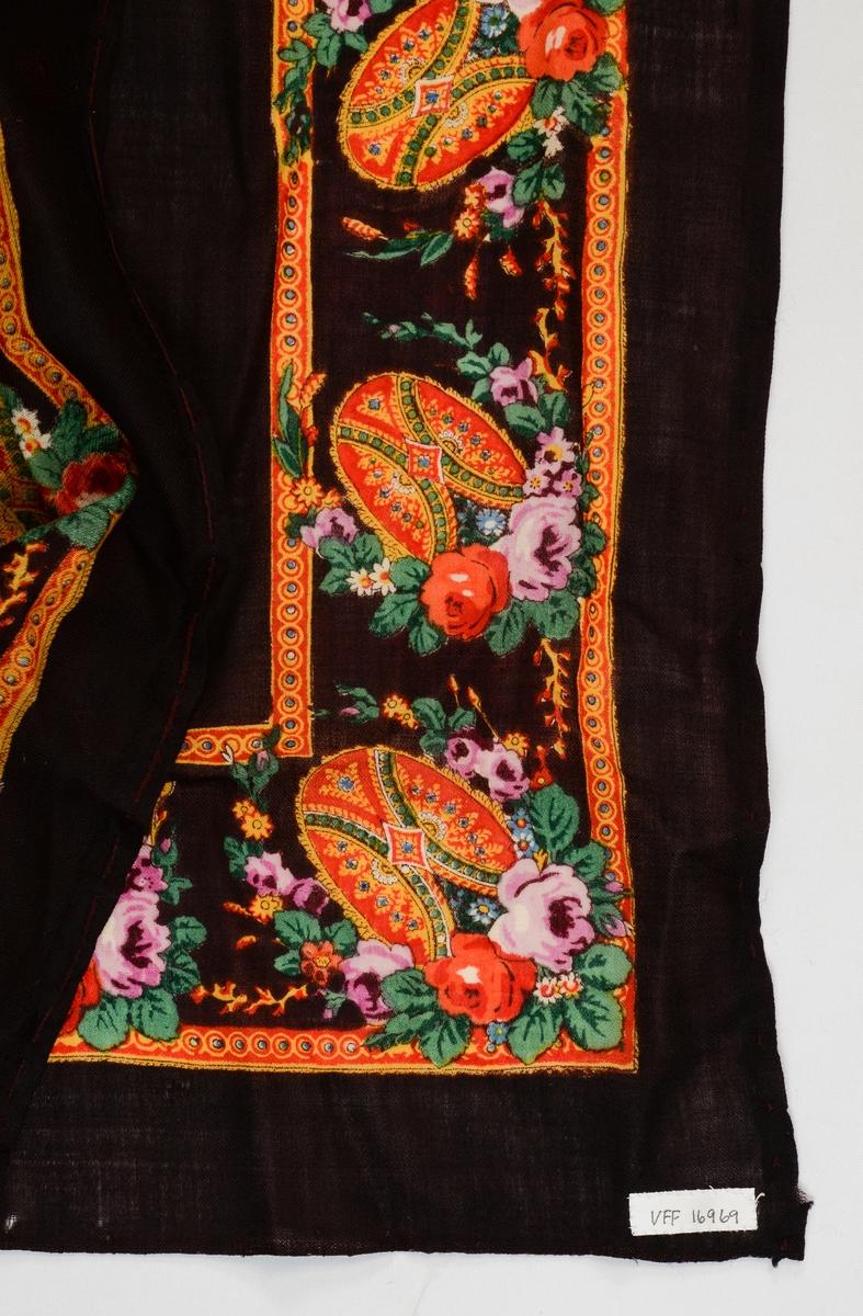 Sjal i brun-svart kypertvove ull med trykt blomsterbord rundt  kanten. To av sidene er falda med lange tråklesting, dei andre har jarekant.