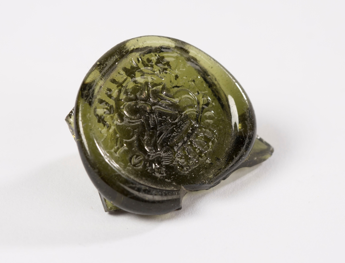 "Ovalt glassegl, med spor av flasken på baksiden. Øverst på seglet en krone. Under dette Fredrik 5. monogram. F5 speilvendt og flettet. Rundt monogrammet står ""NORDSKE COMP 1760"""