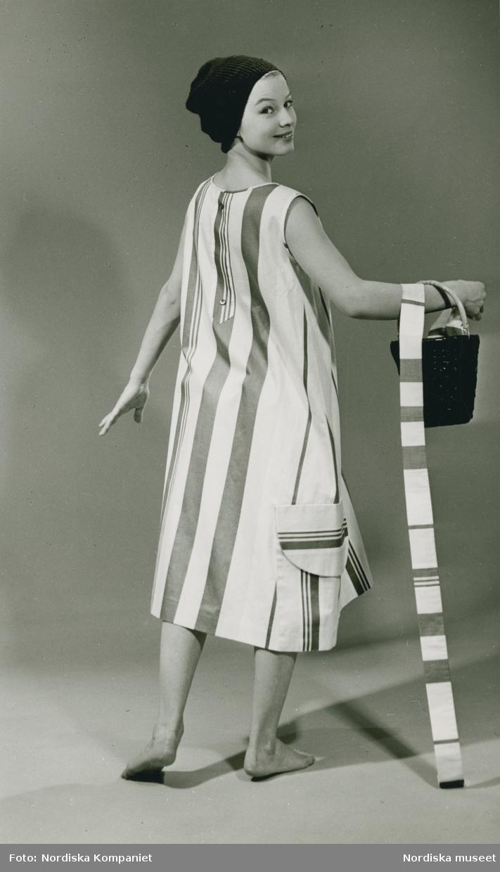 Brud och Hem. Modell i randig klänning, mössa och hink på armen.