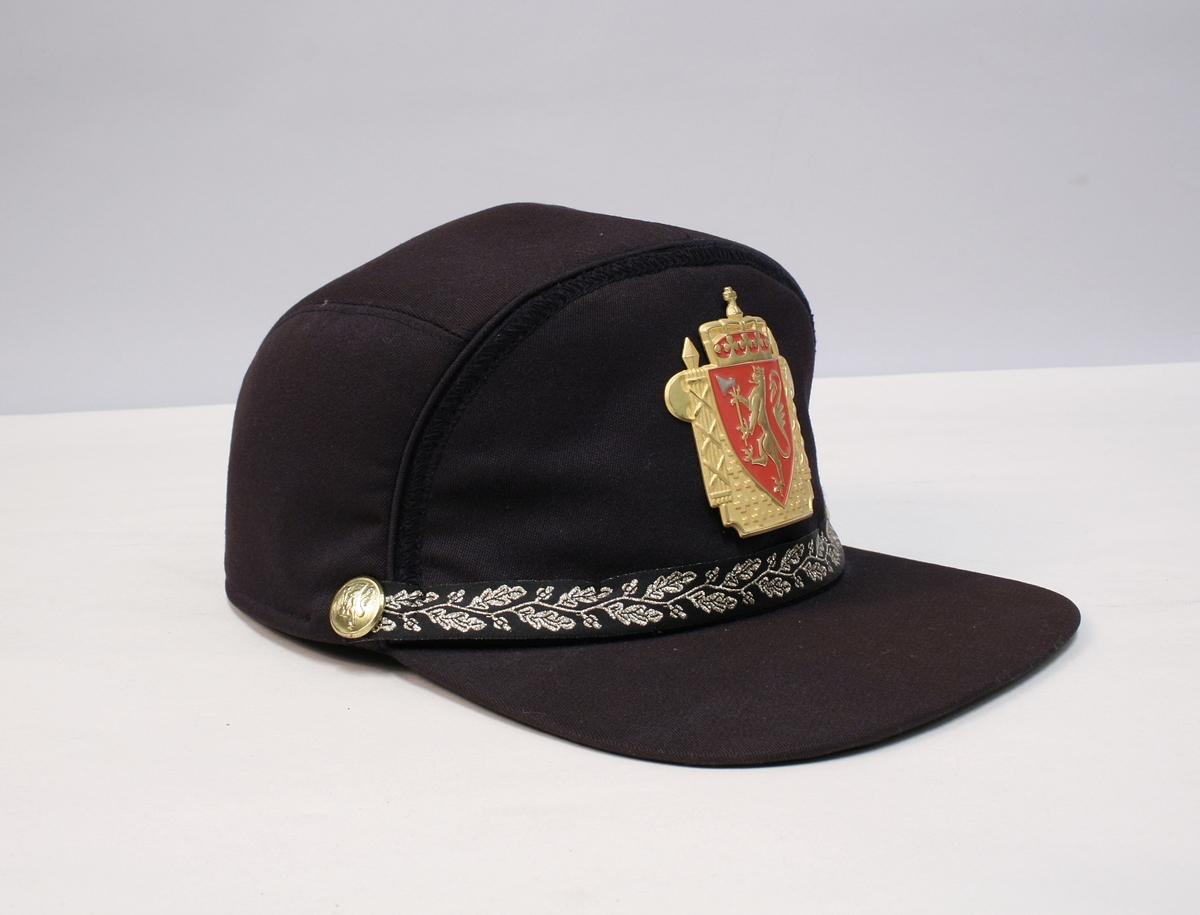 Caps med riksvåpenet i metall foran, ekebladbånd festet med riksløveknapper. Luen har ørebeskyttende flaps som kan brettes ned.