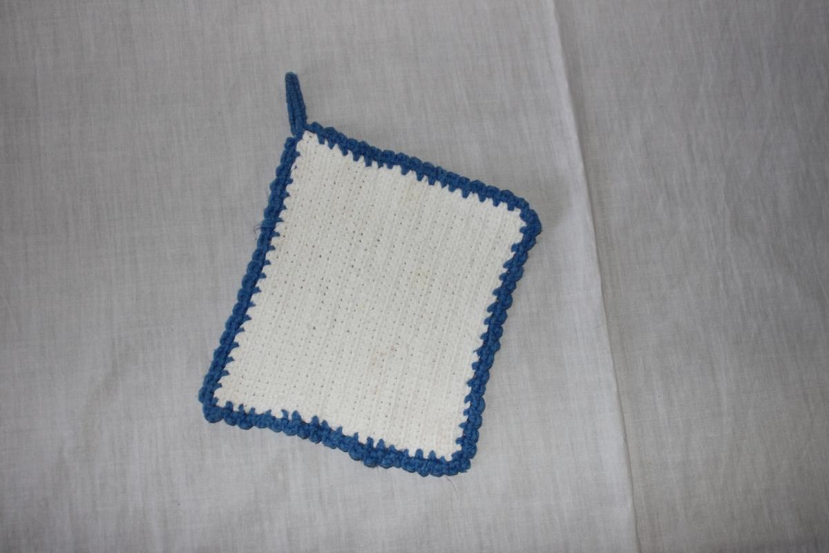 Något rektangulär grytlapp, virkad med fasta maskor, i vitt och blått bomullsgarn. Dekorkant (uddkant) och hängögla i blått garn.