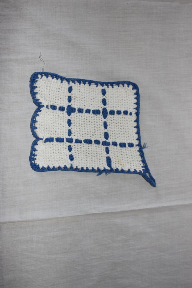 Något rektangulär grytlapp, virkad med fasta maskor, i vitt och blått bomullsgarn. Hängögla i ena hörnet. Rutmönster trätt med blått garn i maskorna. Dekorkant och upphängningsögla i blått garn.