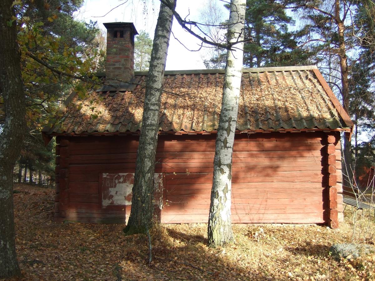 Grunden utgörs av fyra hörnstenar på vilka byggnaden vilar. Väggarna är av liggande timmer med utknutar. Spismuren är synlig i norra och västra fasaden Sadeltaket är lagt på fem runda åsar. Undertaket består av omlott lagda brädor, faltak, med täckning av äldre, enkupigt tegel.  Skorstenen i murat tegel är krönt med plåt upptill och har rökhål på sidorna. Nederst mot taket är den skodd med plåt. Södra gavelfasaden har en lucka av plank, hängande på gångjärn i ena sidan. På östra långsidan finns en plankdörr med låshasp och hänglås. Gångjärnen är smidda, de övre med näbb. Interiört finns en öppen härd i nordvästra hörnet, murad av tegel samt putsad. Öster om denna finns en blåsbälg. Innergolv saknas, marken är täckt med grövre grus.