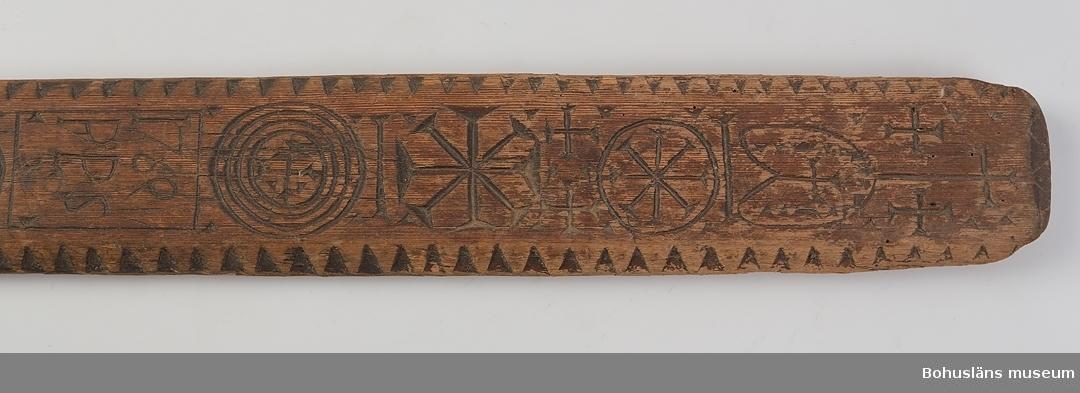 """Platt, rektangulärt redskap med handtag. På ovansidan har den bl.a. skuren karvsnittsdekor med malteserliknande kors, vitterkors, cirklar med inskrivet kors samt en rosett. I mitten är en ruta med årtalet """"1769"""" och ägarinitialerna """"PPS"""". Längs den avfasade kanten löper en uddsnittsdekor som är svärtad. Bakom handtaget är några tvärgående ränder inskurna. Handtaget är något spolformat och ser ut att vara sekundärt. Betsen är avsliten på många ställen. Något defekta hörn. Kavelrullen att linda tyget runt saknas. Skadedjursangrepp.  Litt.; Nylén, Anna-Maja, Hemslöjd, Håkan Ohlssons förlag, Lund, 1978, s. 359-363. Fredlund, Jane, Stora boken om livet förr, ICA-förlaget, Västerås, 1981, s. 40-49. Sörensen, Steinar, Mangletreet-Glatteredskap og festegave, Glomdalsmuseets småskrifter nr. 3, Engers Boktryckeri A/S, Otta.  Ur handskrivna katalogen 1957-1958: Kavelbräde. dat. 1769 """"P.P.S."""" Mangelbräde. L. 83 Br. 9 Trä med karvsnittsmönster. Helt. Handtaget sitter löst.  Lappkatalog: 72"""