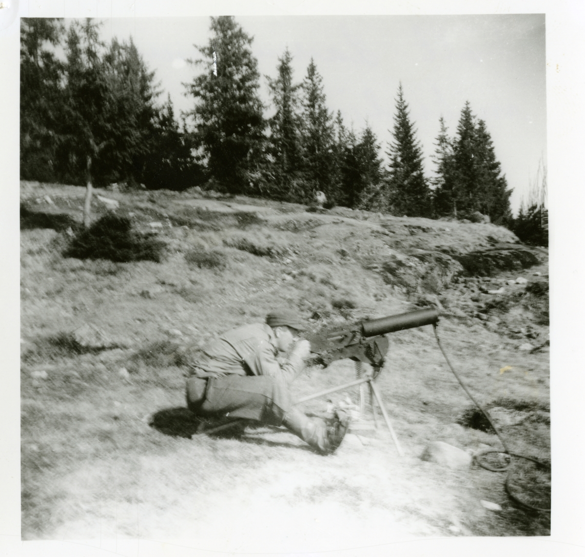 Bjarne Holst Larsen i Hjemmefronten ved ei mitraljøse, foten er laga av Sigurd Berger, av vannpostrør. HS-kurs i Reinsjødalen, Nysetra i 1944.