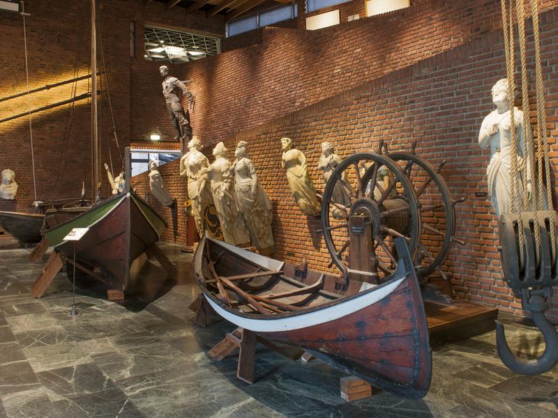 Tre trebåter, ni gallionsfigurer og et ror innendørs i sentralhallen i museet.