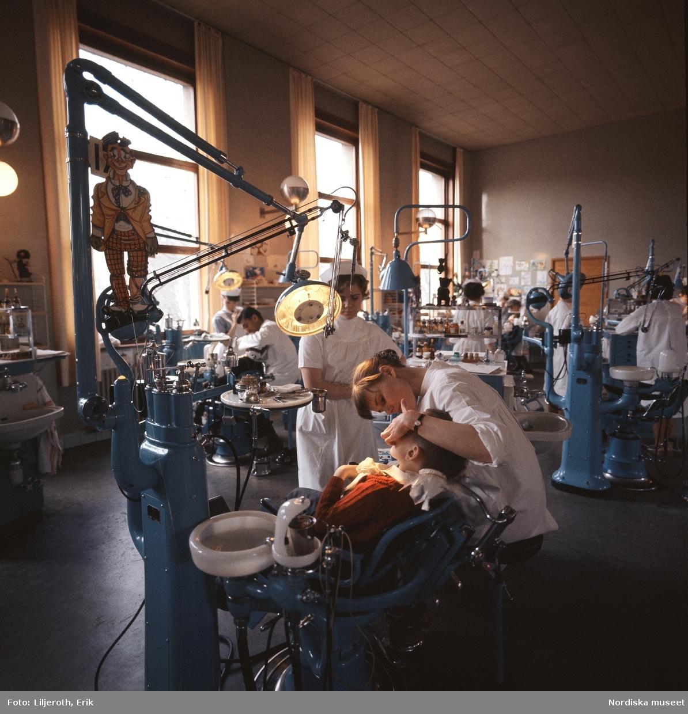 """""""Stockholm"""" . Barntandvård. Tandläkare och tandsköterskor med patienter i stor sal."""