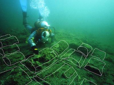 Arkeolog i dykkerutstyr registrerer kalktønner på sjøbunn, tønnene er tegnet opp med hvite streker på fotoet.
