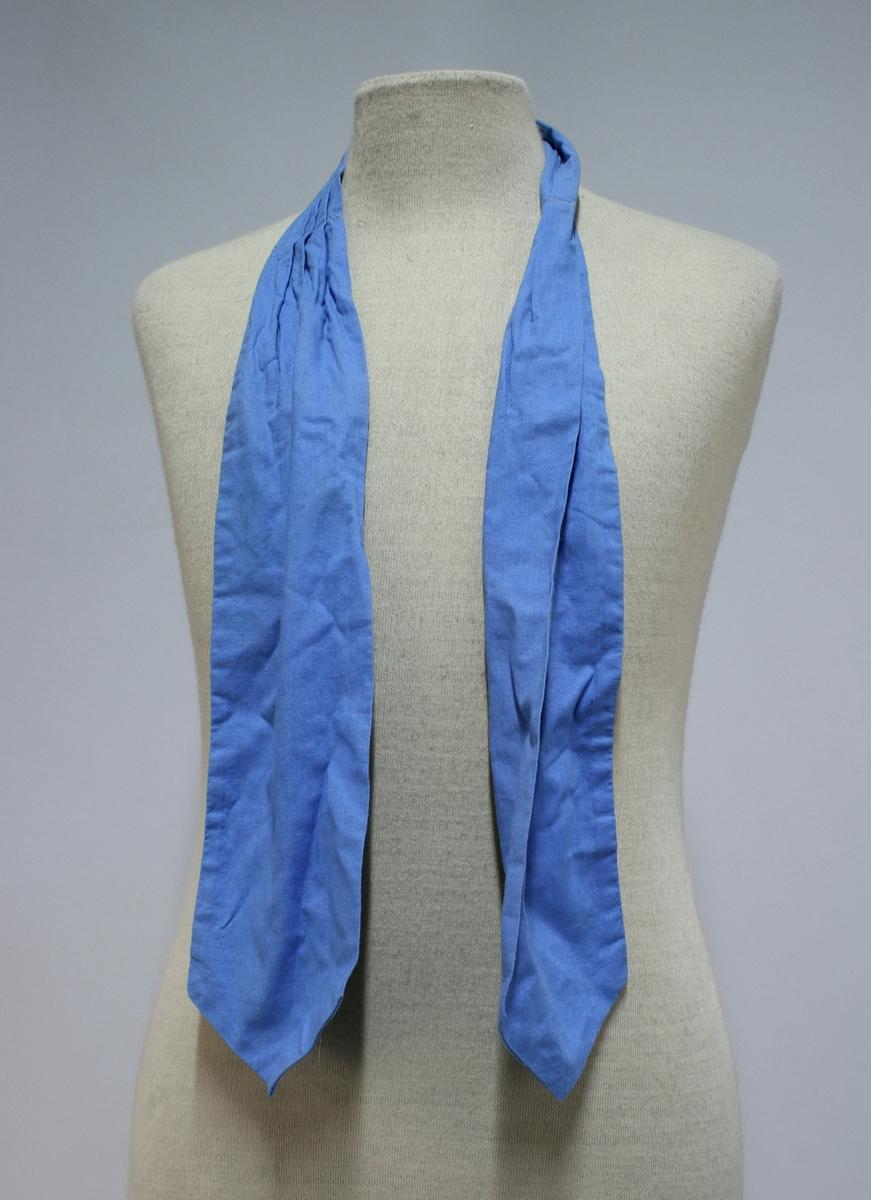 Blå kortermet skjorte med cravat/slips. Skulderdistinksjon for politiførstebetjent.