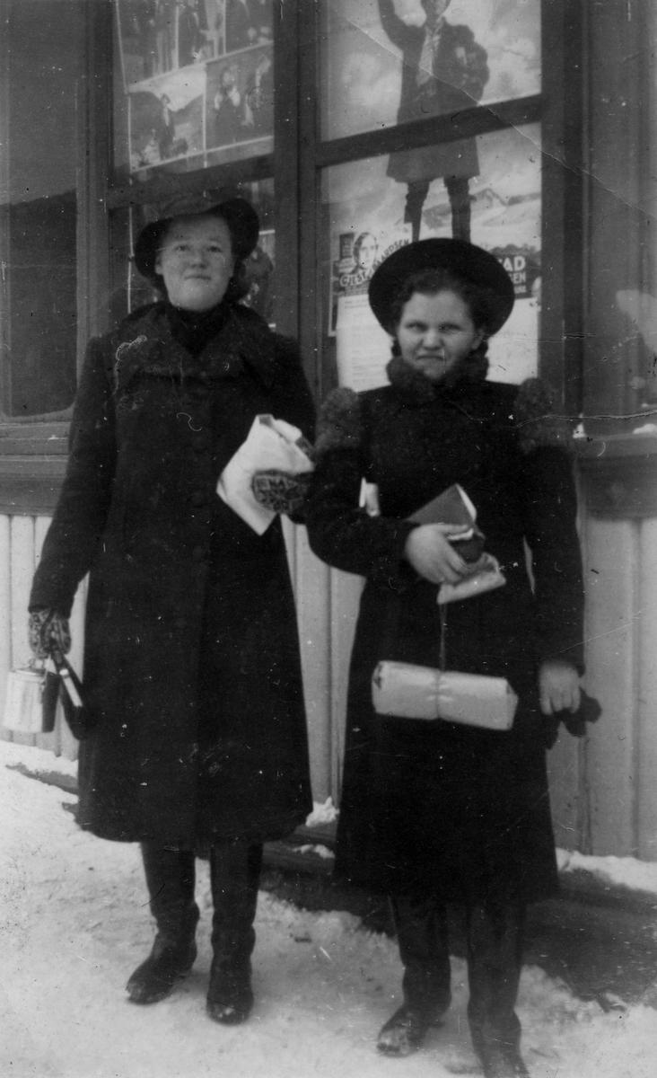 Ruth Kandola (t.h.) sammen med en annen ung dame, avbildet foran det som tilsynelatende må være en butikk. I vinduet bak ses diverse plakater.