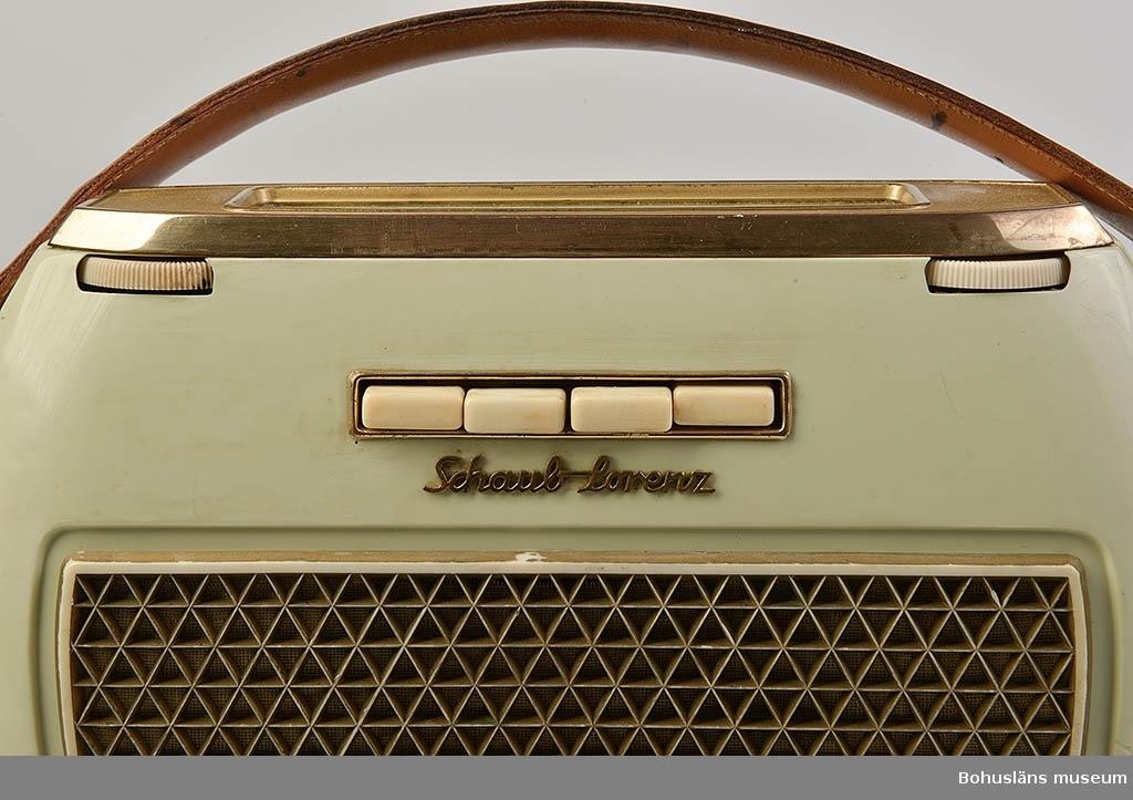 """Ljusgrön transistorradio av fabrikat Schaub-Lorentz, Pforzheim, Tyskland. Fyra vita knappar och högtalare fram. Vridbara programväljare på ovansidan med olika våglängder utmärkta. Två hjul att ställa  in program med. Kortsidorna har rundad form. Bärhandtag av brunt läder. På baksidan står det: """"TRANSISTO..."""". Batteri, 4 st 1.5 volt, modell RZ0."""