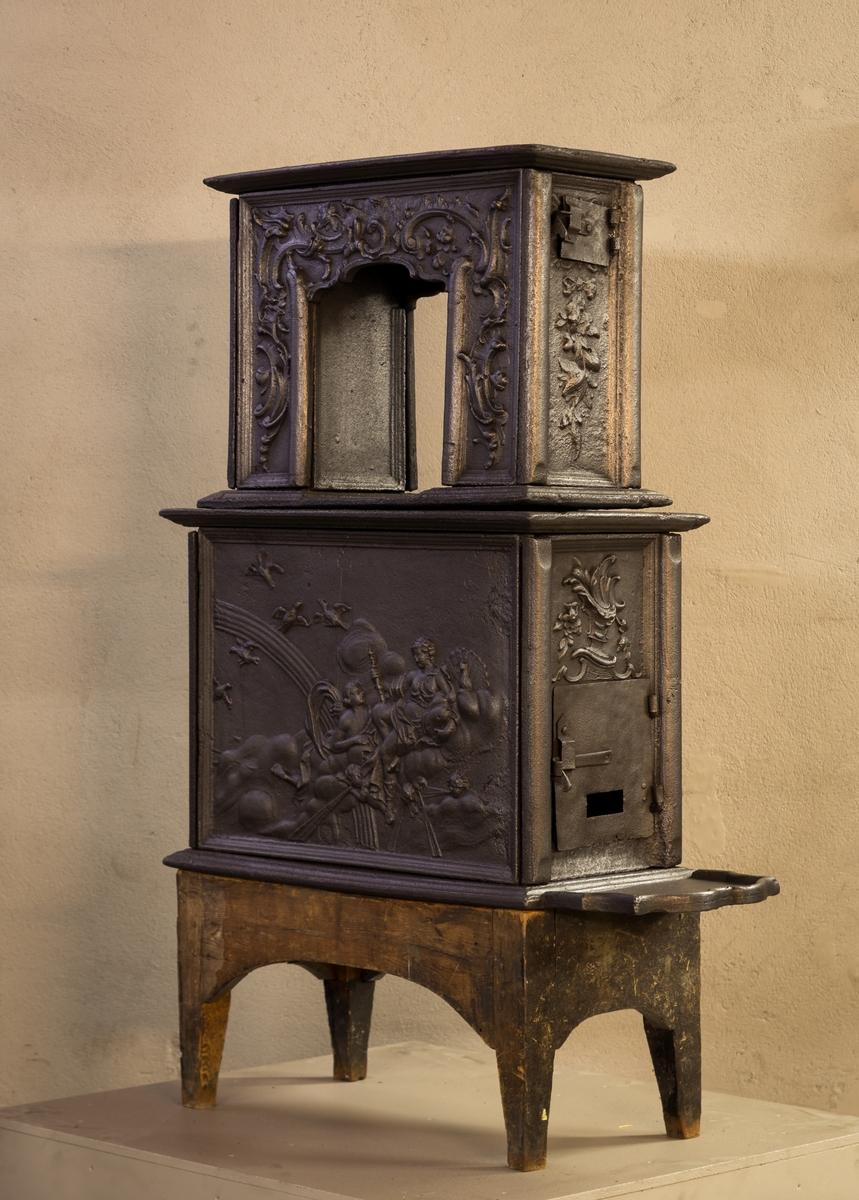 To etasjes ovn med ovnsdør på kortside og røykuttak i topplaten. Langside 1.etg Gudenes sendebud Iris (karakterisert ved regnbuen) bringer et budskap til Juno. Kortside 1.etg Påskrift. Ls. 2.etg Uregelmessig åpning, rokokko-ornamentik. Ks. 2.etg Blad og blomster i sløyfe.