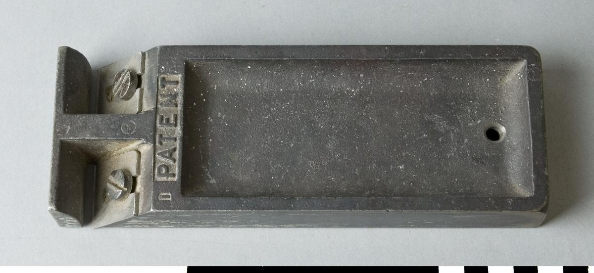 Simshyvel i gjutet utförande. Hyveln utgörs av en gjuten platta, där den främre delen är vinklad för hyveljärnen. Två 28 mm breda hyveljärn är monterade i ytterkanten på hyveln. Mellan dem går en brygga framåt som avslutas med en plogliknande rak platta. På hyveln är texten PATENT ingjuten. Avsedd för hyvling intill en uppåtstående kant. Den är ej märkt med Stockholms Borgargilles nummer.  Funktion: Smal handhyvel, lämpad för putsning i hörn och intill kanter