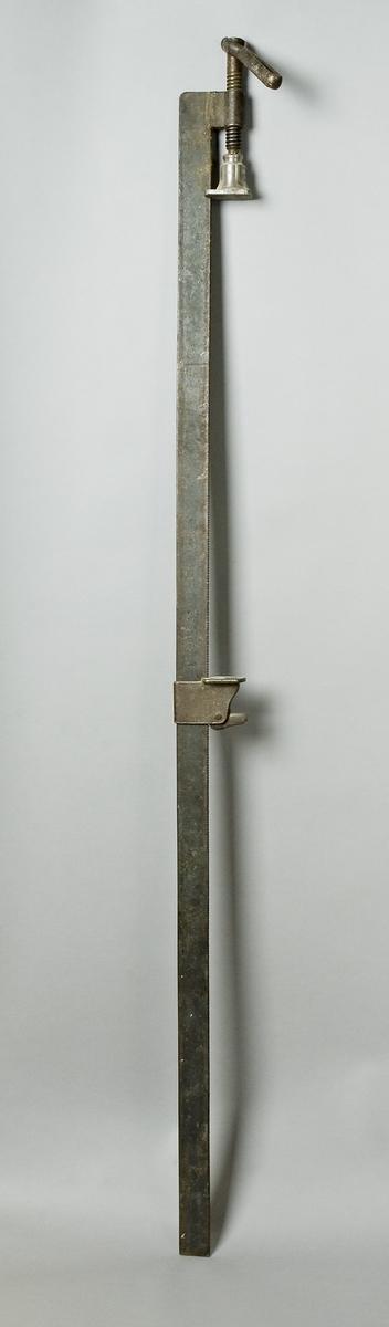 Limknekt av järn. Knekten består av ett långt platt järn i vars ena ände ett kort beslag är fastsvetsat i rät vinkel. Genom den övre delen av beslaget går en kort stålspindel som skruvas parallellt med järnet på dess smala innersida. Spindeln avslutas med en fyrkantig platta med ett urtag nedtill som löper på järnets innersida. I spindelns andra ände sitter ett handtag som är ledat för att lättare åstakomma press vid limning. På det långa plattjärnet finns en flyttbar sadel. Sadelns nedre del har formen av en hylsa som löper på plattjärnet. I sadelhylsans bakre del finns en fjäder fäst i en låsarm som med sin räfflade nedre del i låst läge ligger an mot plattjärnets likaså räfflade innersida. Genom att fjädern spännes, släpper låsningen och sadeln kan flyttas.  Funktion: Hålla ihop delar som limmas