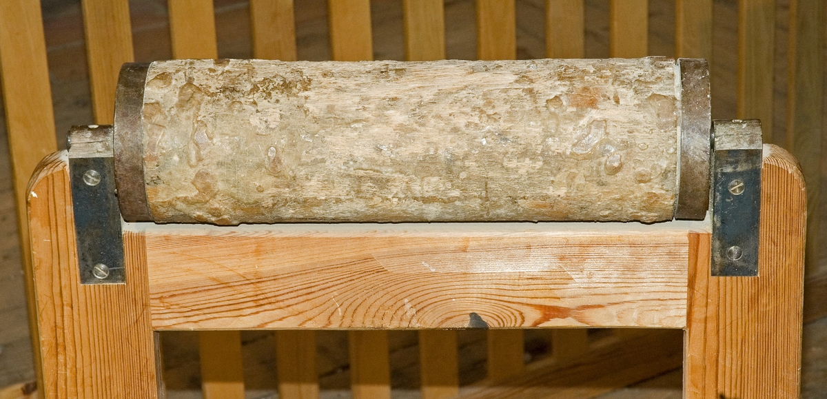 Materialstöd bestående av en bock med en rulle monterad överst. Den övre delen av bocken är höj- och sänkbar. Två kraftiga järnhandtag på genomgående bultar i vardera stativbenet kan vridas för att spänna fast den övre delen i önskad höjd. Denna löper genom spår i den undre delen. Bockens övre del är nytillverkad. Rullen och den nedre delen av bocken är delvis täckta med ett lager torkat lim.Materialstödet kommer från Misterhults Möbelfabrik i Figeholm i Småland.   Funktion: Utbyggnad av arbetsyta