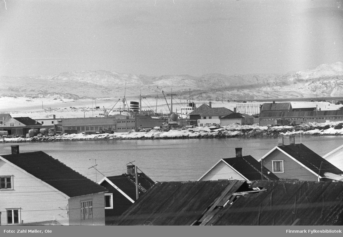 Fotoserie fra Vadsø, April 1968 fotografert av Vadsøfotografen Ole Zahl-Mölö. Utsikt fra hustakene på Vadsøya. I bakgrunnen ser man pipa på det som sannsynligvis er Hurtigruta ved kai i byen. Anløpet var på den tiden i sentrum.