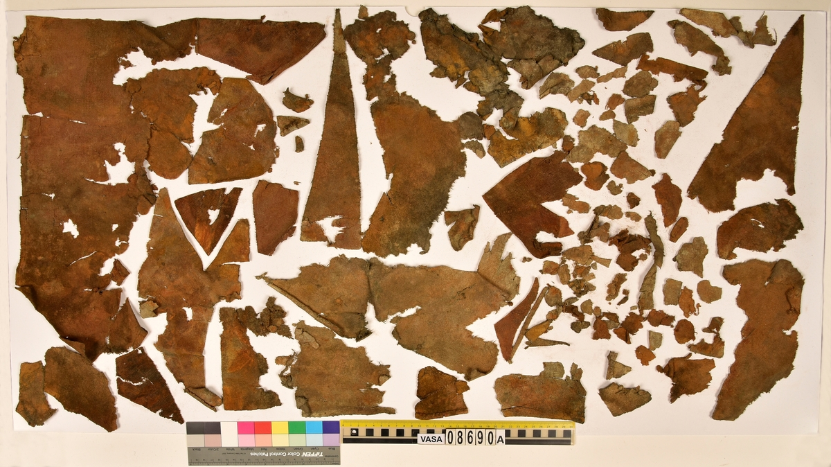 Textilier. Styvt. Fragmenten är uppdelade på fyndnummer 08690a-b. Fnr 08690a består av ca 120 fragment av ull vävt i tuskaft. Tyget kan ha varit valkat på ena sidan. Fragmenten är styva av korrosion. Flera av fragmenten har delvis bevarade originalkanter samt en del sömmar med tråd kvar. Fnr 08690b består av 5 fragment av ull vävt i 2/1-kypert. Tyget är ljusbrunt men har stora oranga partier pga korrosion. Det största fragmentet består av tre ihopsydda tygbitar.
