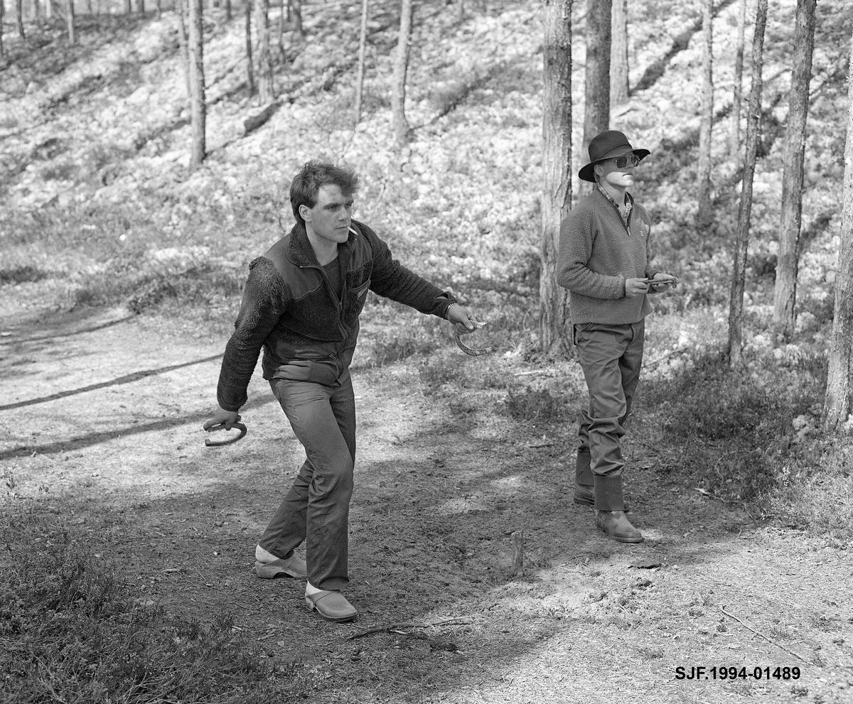 Hesteskokasting ved Stenbekkoia i Engerdal våren 1986. Fotografiet viser to konkurrenter, begge med hestesko i hendene. Martin Myhr til høyre. En av karene var i ferd med å kaste da bildet ble tatt, mens den andre fulgte spent med. Målet for kastinga var en trepinne som stakk 10-15 meter over bakken på ei plan grusslette noen meter fra kastestedet (jfr. SJF.1994-01487 og SJF.1994-01488).  Den som kastet nærest pinnen, eller eventuelt fikk hesteskoen til å omslutte den, lå best an i konkurransen.  Deltakerne kastet fra samme punkt og disponerte vanligvis to hestesko i hver omgang.   Det skal særlig ha vært de yngste fløterene som hadde hesteskokasting som fritidssysel om kvelden.