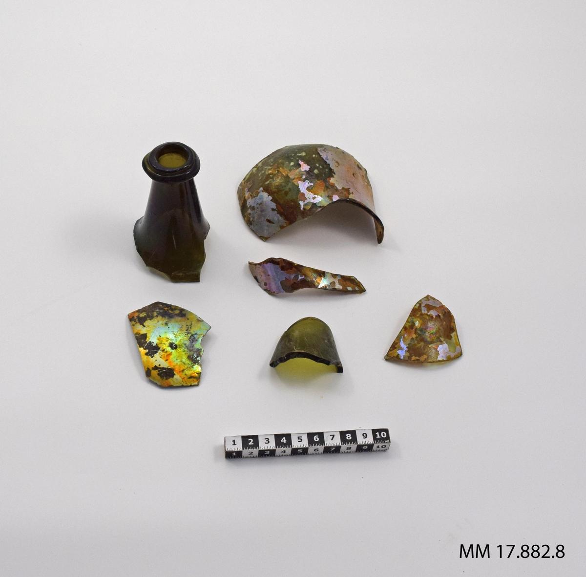 Sjöfynd från vraket Nya Riga. Glas, femton stycken mindre fragment, iriserande, ett större samt en flaskhals.  För dimensioner på den enskilda bitarna, se inventariebilaga.