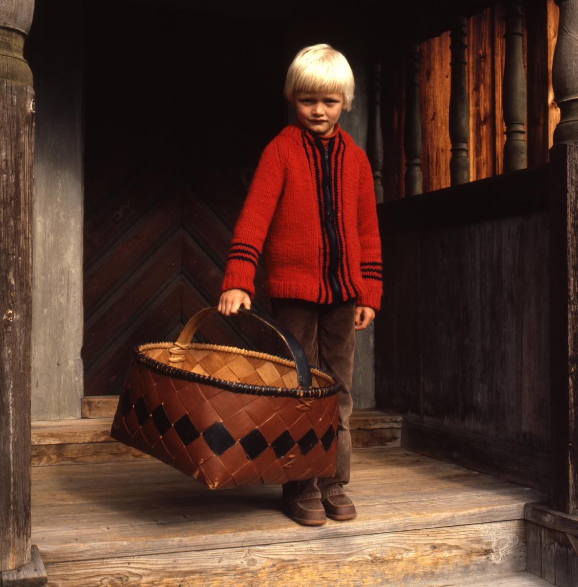 Ett barn i röd stickad kofta står på en gammal förstukvist med en stor spånkorg i handen.