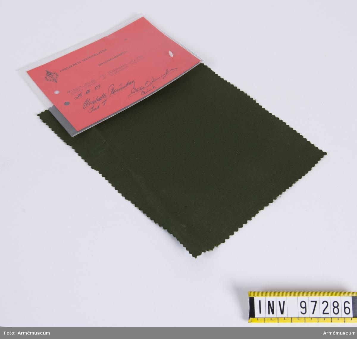 """Vidhängande modellapp med text: """"Försvarets materielverk. Originalmodell. M 1016-238140-9. Vindpoplin 140, Grön M 106-238150-8 Vindpoplin 150, Grön. 1985-08-07. Elisabeth Rönnberg IntT, Göran Olmarker QInt."""""""