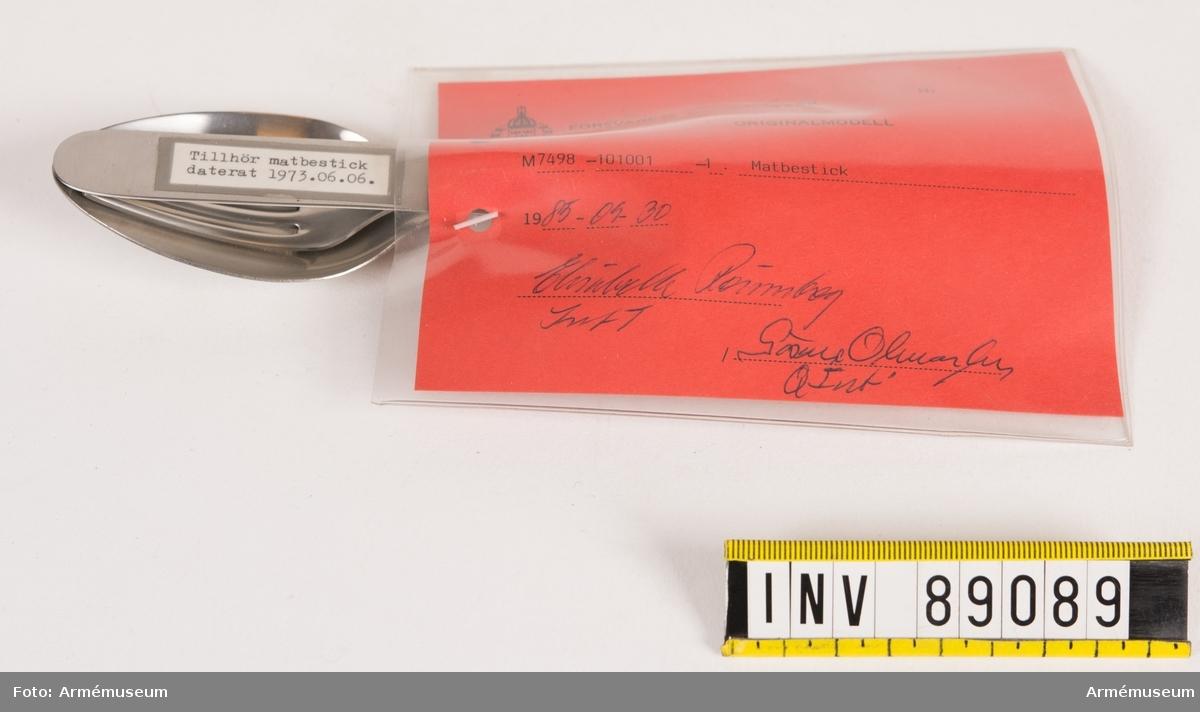 """En uppsättning matbestick bestående av kniv, sked och gaffel. På varje bestick  finns en tre kronor-stämpel och texten """"Gense 18-8 Stainless Sweden"""". På knivens ena sida är en maskinskriven pappersetikett med texten """"Tillhör matbestick daterat 1973.06.06. fasttejpad. Vidhängande modellapp med text: """"Försvarets materielverk. Originalmodell. M 7498-101001-1 Matbestick. 1985-09-30. Elisabeth Rönnberg IntT / Göran Olmarker QInt."""""""