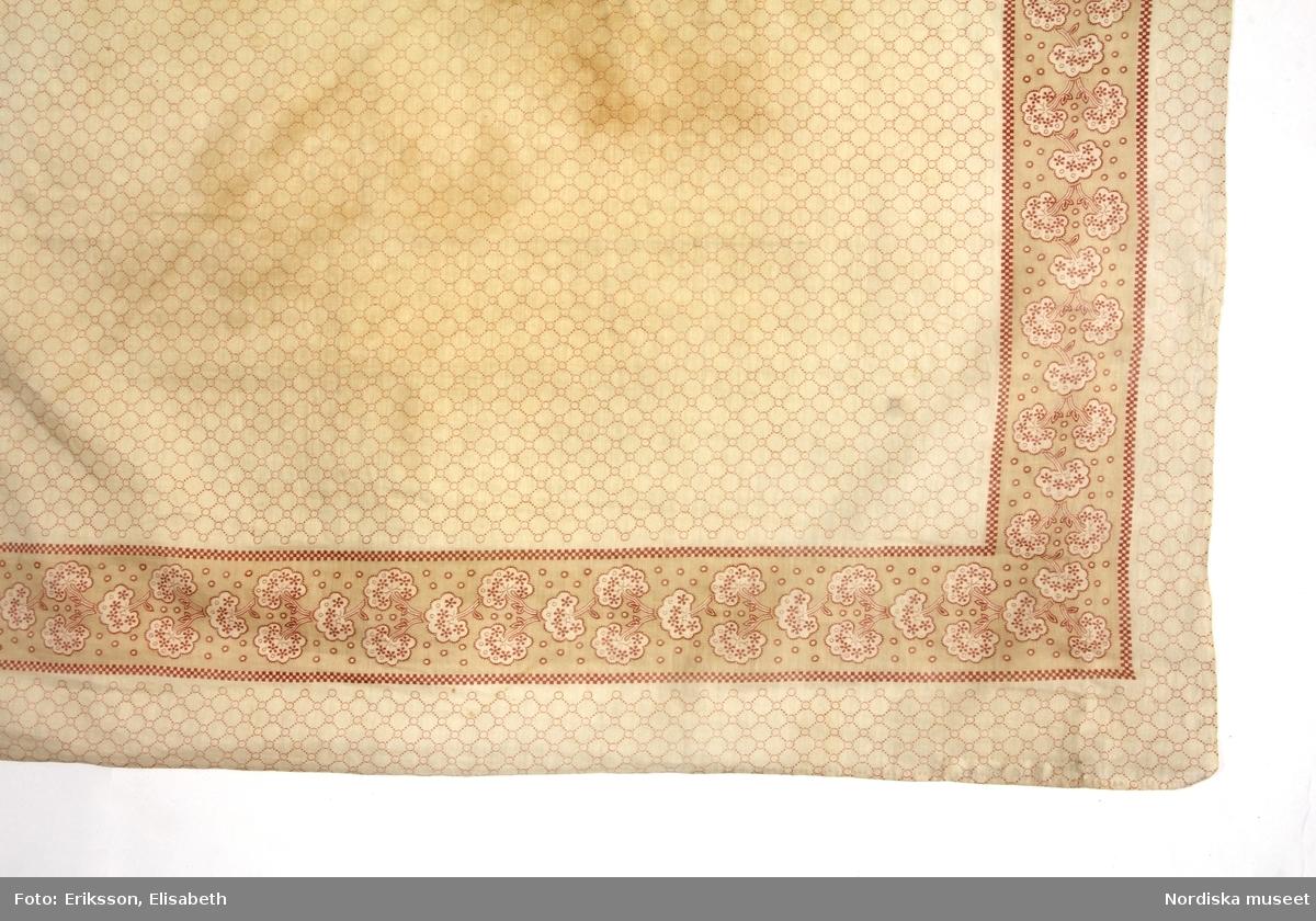 Kvadratiskt hals- eller huvudkläde av tunn bomullslärft, vit med svagt mönstertryck i ljusrött, i spegeln ett bikakemönster med prickade ränder, smal kantbård med buskliknande mönsterformer med utfyllnad av små ringar runtom i rött och vitt på ljust beige botten. 3 handsydda fållar, en stadkant Anm. Sliten och  med en stor gulnad fläck. /Berit Eldvk 2012-01-24