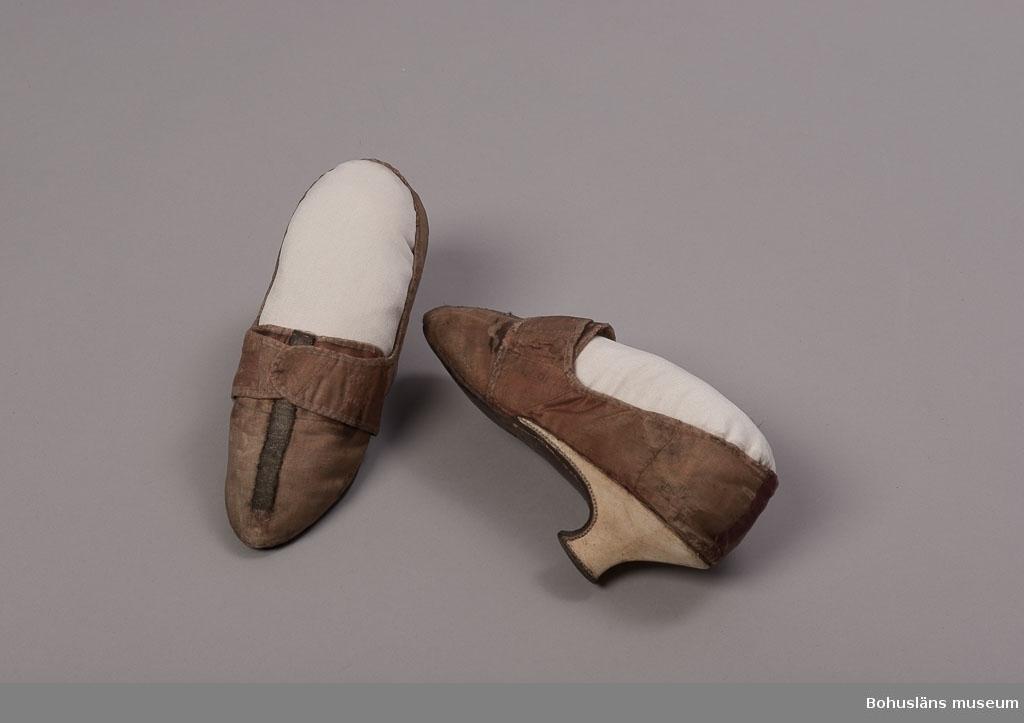 """Damsko från 1700-talets senare hälft, slejfsko, med smal tå, på ovansidan dubbla slejfar ovan en plös samt med halvhög klack.  Skon överklädd med rödgult bleknat siden som tidigare varit rött (""""hallonrött""""; kan ses under slejfarna). Bandkantad runt kanterna. Längs ovansidan ett dekorband av guld- eller silverbrokad. Bakkappan har troligen haft liknande dekorband men detta är ersatt med ett rött sidenband på höger sko och en lagning på vänster. Klacken är överklädd med vitt blankt skinn. Läderbindsula. Invändigt klädd med ofärgat linne, sula och bakkappa klädda med barkgarvat skinn. Skorna har hållits samman med skospännen eller band, kanske med rosetter. På ena innersulan äldre anteckning i bläck: År 1784. Mycket slitna.  Äldre etikett med anteckningen: """"Brudsko av siden fr. 1784. Gåva av H. överstelöjtnant Hjortsberg.""""  Ur handskrivna katalogen 1957-1958: Ett par brudskor fr 1700-t. Sulornas L. c:a 22,5 cm. Siden, rödgult. Sulor av läder, klackarnas utsida av vitt skinn. Tyget trådslitet o mycket blekt. Fr. 1784, Simmersröd.  Simmersröd egendom i Ljungs socken donerades 1859 till barnhus av ägaren Sven A. Bergius (1797 - 1864). Gården var enligt osäkra uppgifter en tid häradshövdingens gård."""