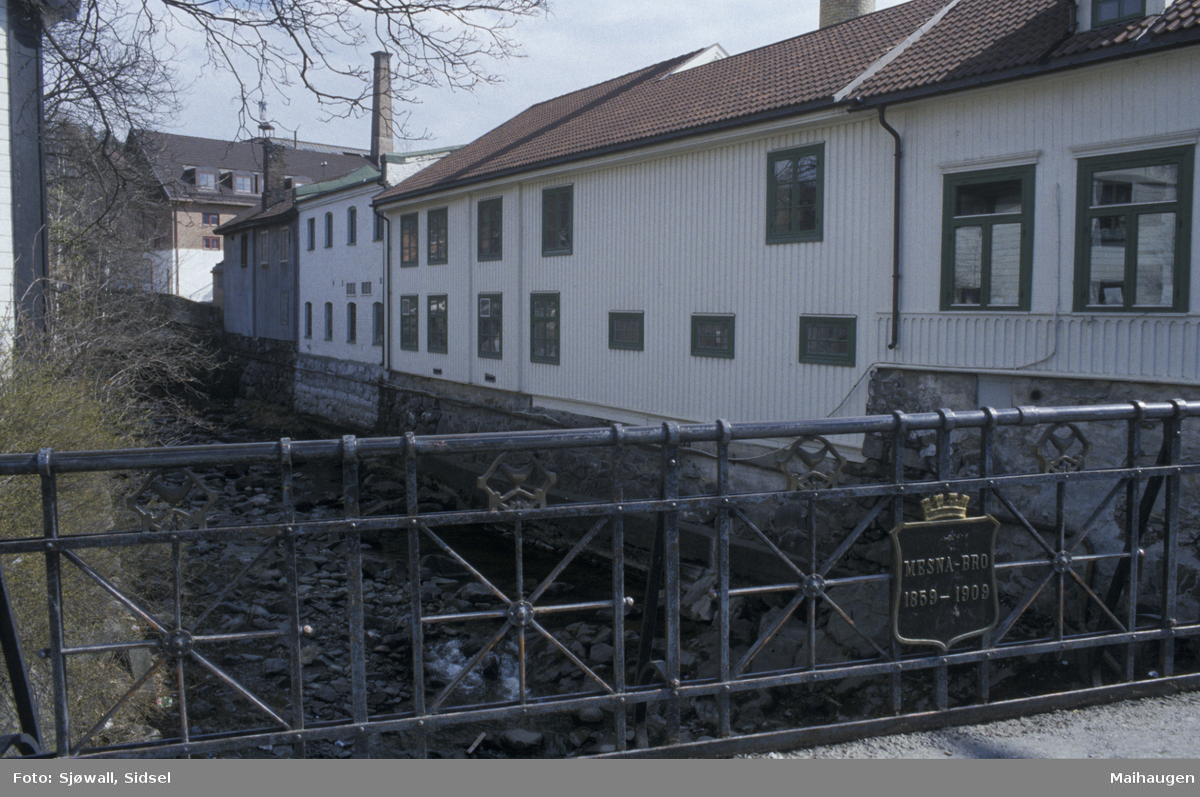Lillehammer, sentrum, bebyggelse ved Mesnaelva på sørsiden, tatt fra Mesnabrua. Bygning til høyre er Storgata 83