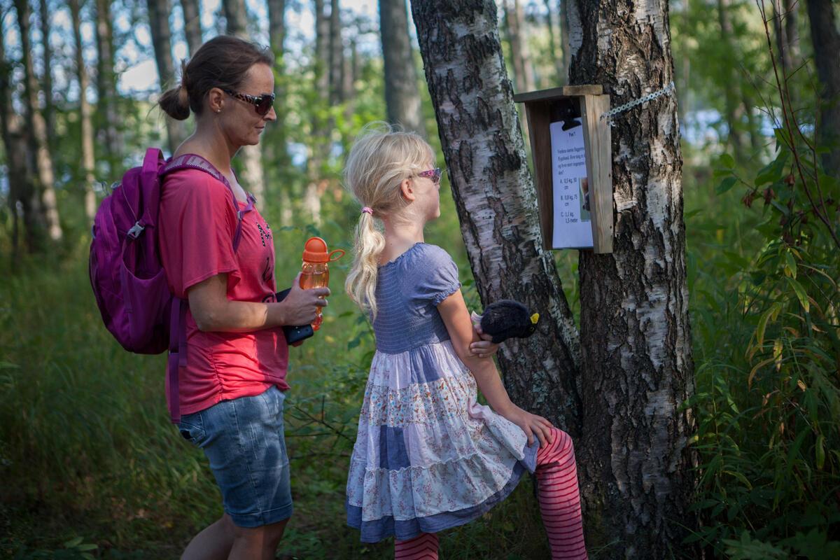 Mor og datter leser på en naturstipost på Blikomøya. Mor har olabukse og t-skjorte på seg og datteren har sommerkjole