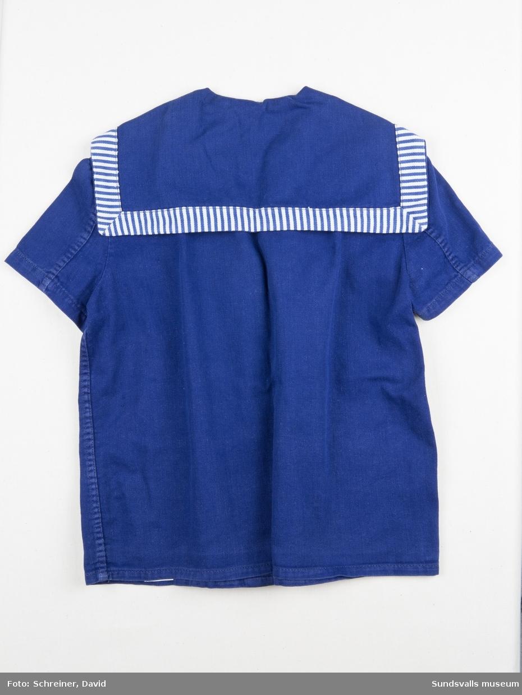 En blå och vit kortärmad jacka med randigt slag samt randig infällning i ovankant av de rundade fickorna. Jackan knäpps framtill med fyra stycken blå plastknappar. Bandet i nacken som används för upphängning bär texten Algots.