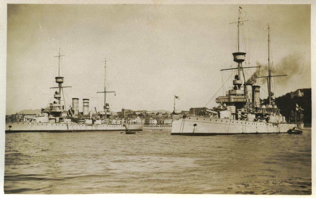 Vykort med motiv av två pansarskepp av Äranklass i stadsmiljö.