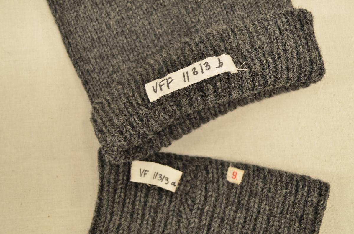 Lange strømper (a+b), maskinstrikket i grått ullgarn. En strømpe stoppet med lyst garn i tå, en strømpe stoppet med grått garn på hæl.
