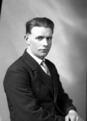 Ateljébild på en man i skjorta, slips och kavaj. Enligt Walt