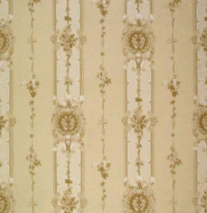 Ett sirligt randmönster dekorerat med kunga- kronor och franska liljan dekorerade medaljonger i diagonalupprepning omväxlande med lodrätt växtranka i sidenband. Tryck i vitt samt i två ljusbruna nyanser på en cremebeige bakgrund.