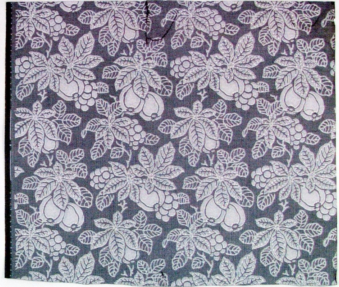 Tätt ytfyllande mönster bestående av äpple, druvor och blad över litet rutmönster. Tryck i vitt på ett grått genomfärgat papper.