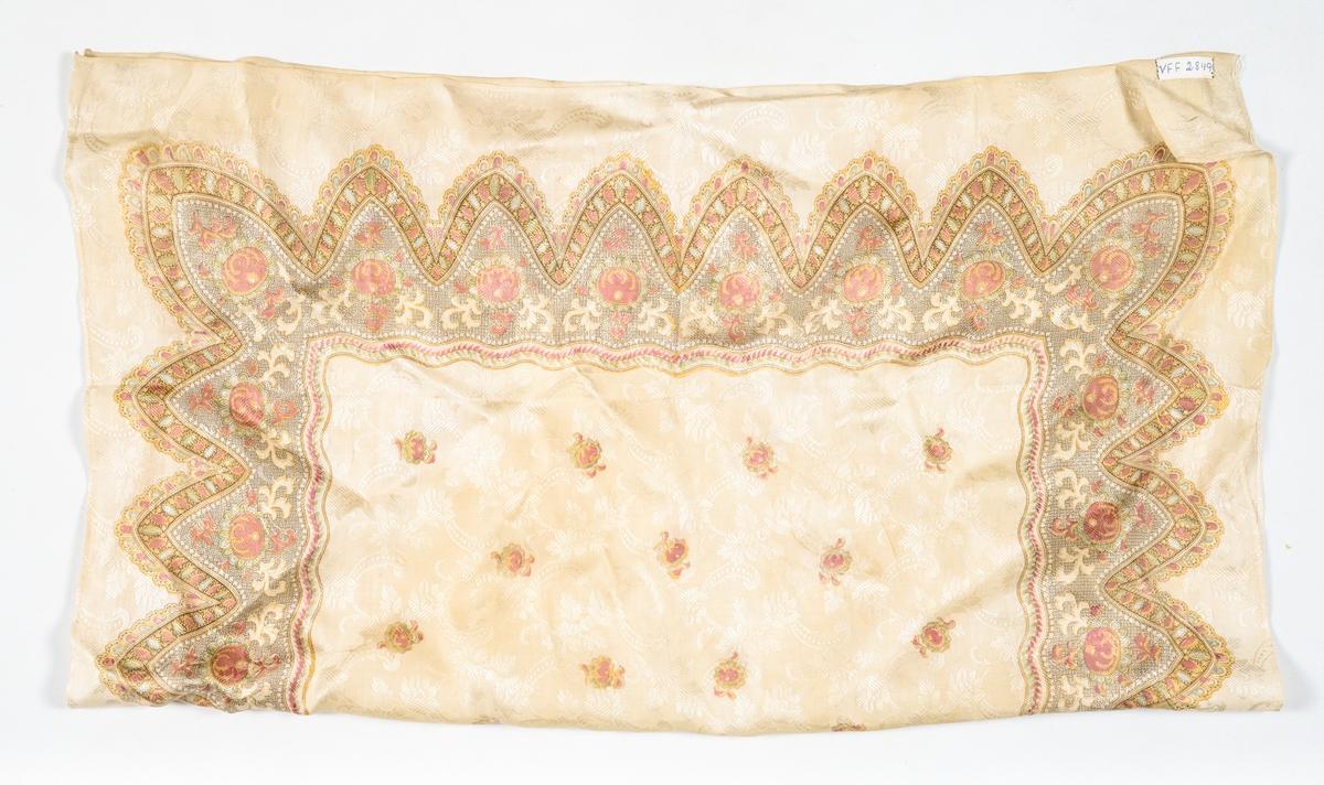 Tørkle i beige silkedamask, med trykt mønster i rosa, brunsvart, gult, turkis, beige og kvitt. Falda for hand med 2 mm brei fald i to sider, jarekant i dei to andre.