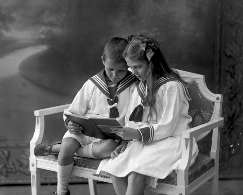 Portrett barn i matrosklær leser bok