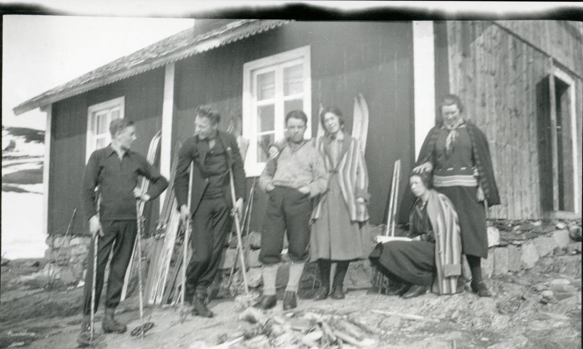 3 kvinner og 3 menn utenfor et stølshus. Skiene står langs veggen.