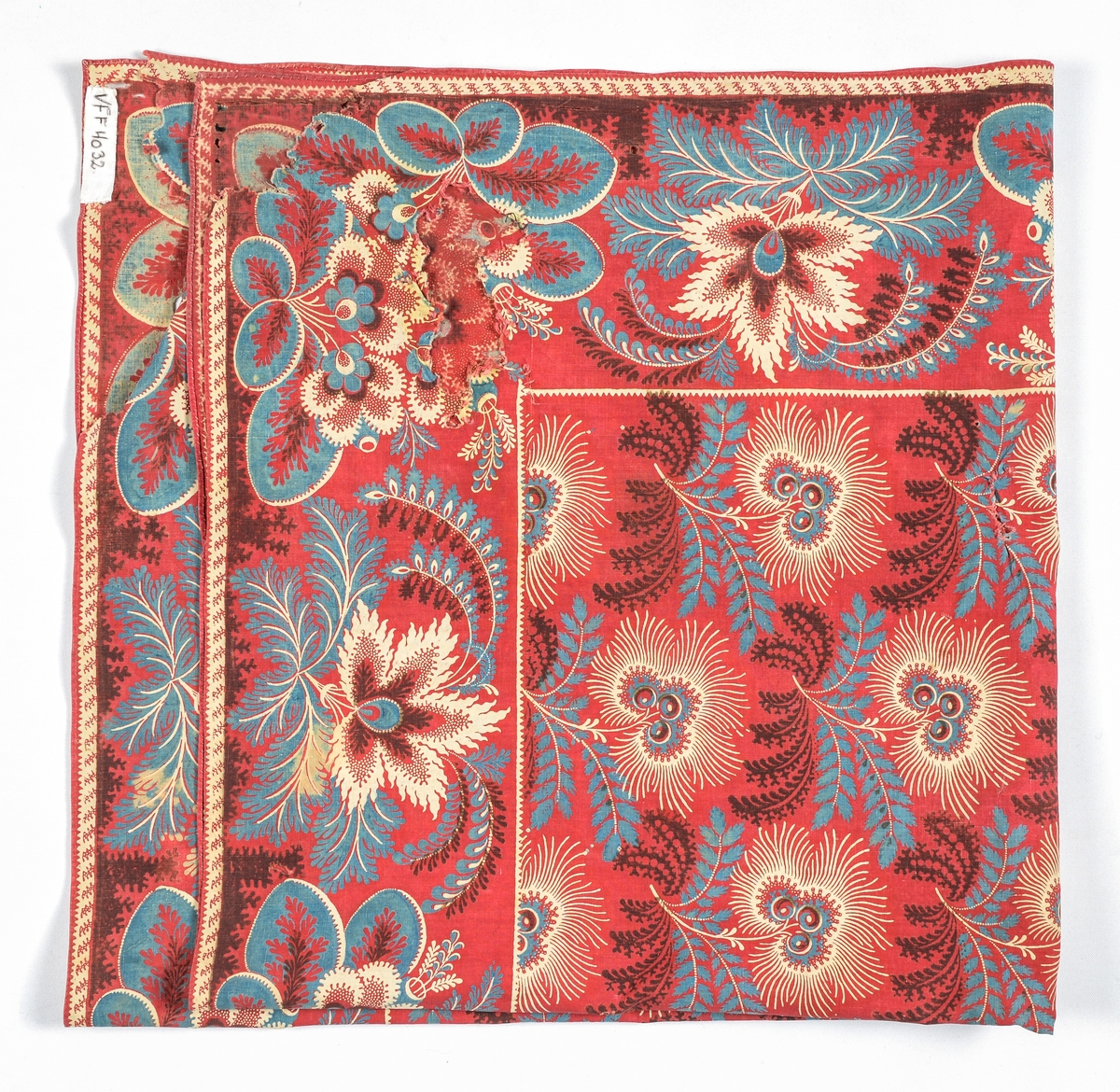 Tørkle i raudt bomulltøy, (tyrkerraudt) i botn, med trykt mønster i blått, burgunder og lys beige. Falda for hand med 1,5 mm brei fald i alle fire sidene.